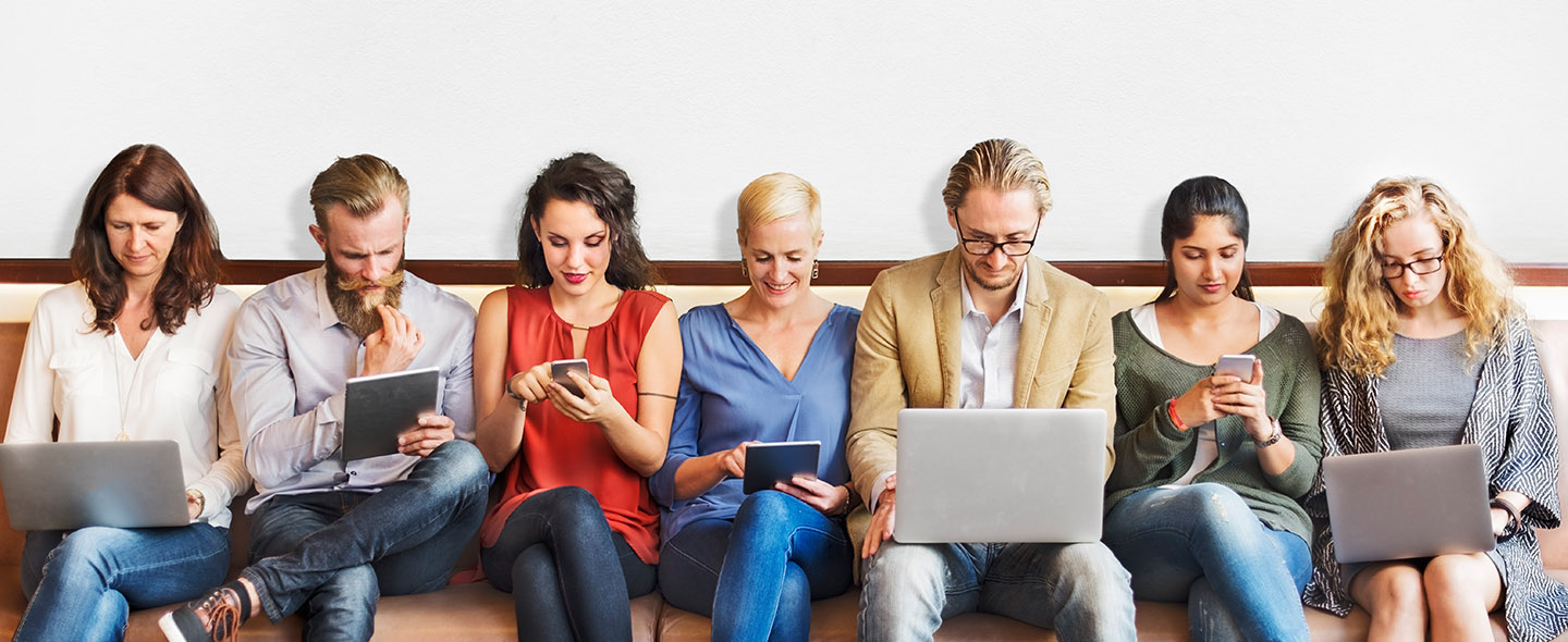 group of people sitting on a couch using their laptops, phones and tablets