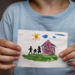 Child holds a drawn house with family